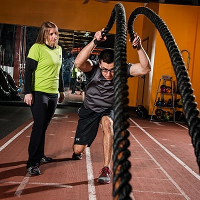 Cal Fit Member Using Battle Ropes with a Body Fit Coach