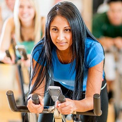 woman in indoor cycling class at cal fit