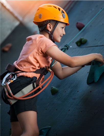 Child rock climbing at Sacramento gym with childcare.
